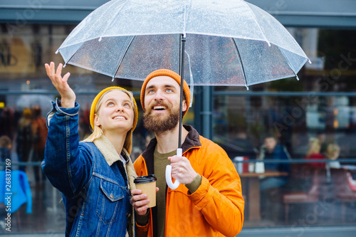 Fototapeta Doesn't stop raining soon concept. Hipster couple under umbrella in rainy spring cold weather urban city street on background. Lifestyle concept. obraz