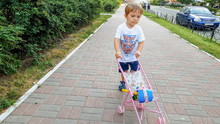 3 Years Old Toddler Boy Walking With Toy Pram On The Street. Boy Playing With Toys For Girls.