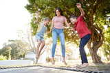 Siblings With Teenage Sister Playing On Outdoor Trampoline In Garden - 268324928