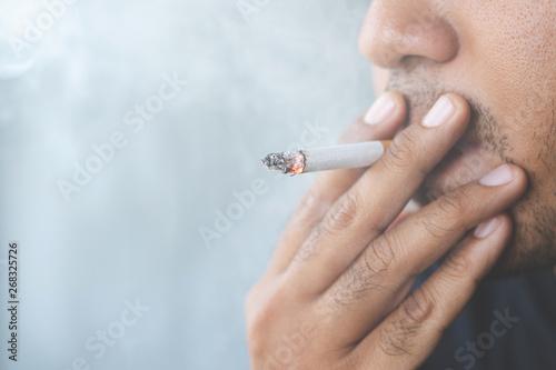 Fotografia  man smoking a cigarette. Cigarette smoke spread.