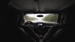 Shot taken from a back seat of a Jeep car showing two men on the front seats and a foggy / rainy day outside along the road - slow motion.