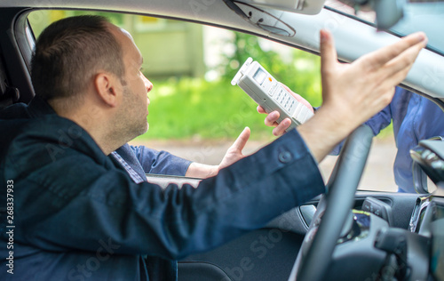 Fotografie, Tablou  Driver due to being subject to test for alcohol content with use of breathalyzer