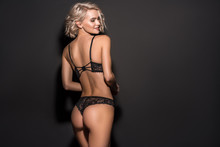 Back View Of Beautiful Sexy Girl In Lace Lingerie Posing On Black With Copy Space