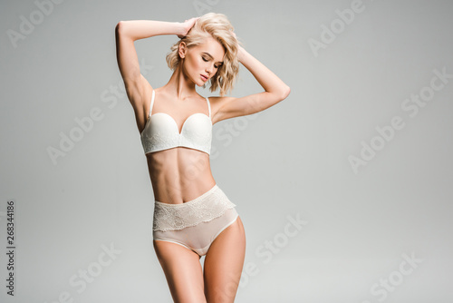 Stampa su Tela beautiful sexy girl in lingerie posing with hands on head isolated on grey with