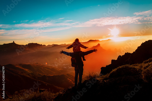Fototapeta father and little daughter travel in mountains at sunset obraz