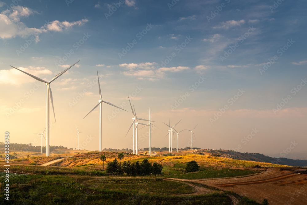 Fototapeta Wind turbines and Orange sunset sky. Beautiful mountain landscape with wind generators turbines,Thailand. Renewable energy concept.