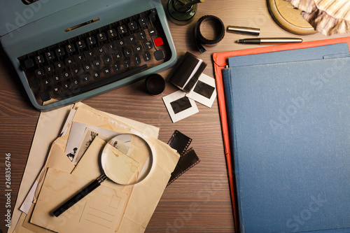 Canvas Print Investigator desk with confidential documents, vintage typewriter, film, magnifying glass and hat