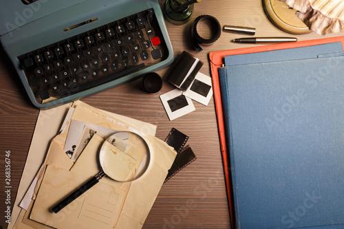 Slika na platnu Investigator desk with confidential documents, vintage typewriter, film, magnifying glass and hat