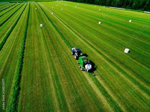Foto auf Gartenposter Grun Aerial view of Tractor mowing green field in Finland.