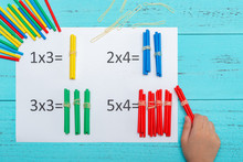 Kid Doing Multiplication Equations Using Counting Rods