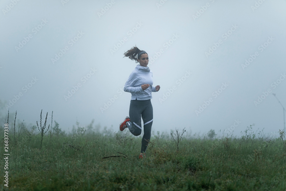 Fototapety, obrazy: Young motivated sportswoman running through foggy meadow.