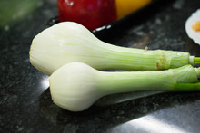 Two Spring Onions On A Black G...