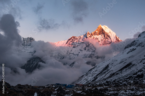Foto auf Gartenposter Antarktika Macchapucchre Himalayan Peak at red and orange sunset with clouds