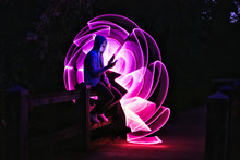 Boy Sitting On A Bridge With His Smartphone In His Hand. Violet Light Effect With A Light Saber In Lightpainting