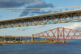 Older Forth Road bridge and the iconic Forth Rail Bridge in Edinburgh Scotland.