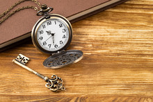 Vintage Pocket Watch Clock With Key And Book On Wooden Background