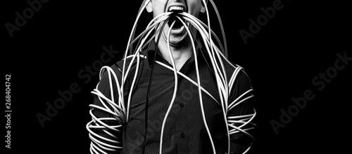 Fotografie, Obraz  a man in a shirt wrapped the wires, the wires go out of his mouth