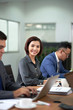 Portrait of Asian businesswoman sitting at the table between her colleagues and smiling at camera during business presentation at office