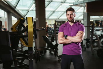 Handsome friendly personal trainer in gym. Young sporty man smiling standing on fitness club background