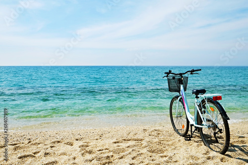 Deurstickers Strand Feminine bicycle of comfort class with empty basket on the sandy beach of mediterranean sea. Blue cruiser bike on sunny day at sea shore with a lot of copy space for text.