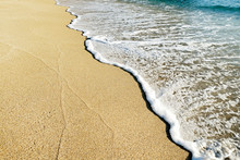 Top View Shot Of Sea Foam On Sandy Beach Shore On Sunny Day. Ocean Scenery With Calm Azure Water And Golden Sand, A Lot Of Copy Space For Text. Close Up.