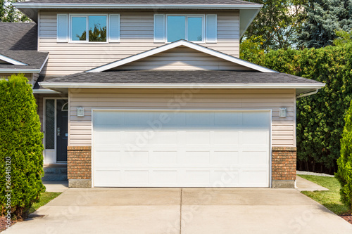 Photo Wide garage door of residential house with concrete driveway in front