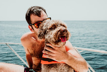 .Young And Attractive Man Enjoying A Relaxing Vacation On His Boat Playing With His Lovely Brown Spanish Water Dog On The Yatch Sunny Summer Day. Lifestyle