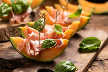 Sliced Melon With Ham And Basil Leaves, Served On A Wood Chopping Board