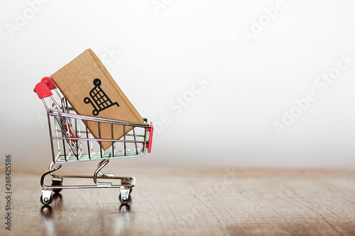 Obraz na płótnie Shopping cart with carton against white background with copy space
