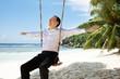 Young Man On Swing Enjoying The Fresh Air At Beach