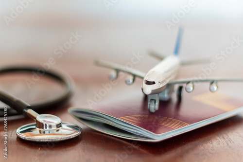 Fotografia  Airplane on top of a passport document and a Stethoscope