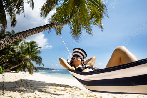 Foto auf Leinwand Texturen Young Woman Relaxing On Hammock Over The Beach
