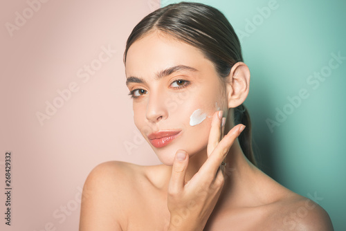 Foto auf Leinwand Spa Beautiful woman spreading cream on her face. Skin cream concept. Facial care for female. Keep skin hydrated regularly moisturizing cream. Fresh healthy skin concept. Taking good care of her skin