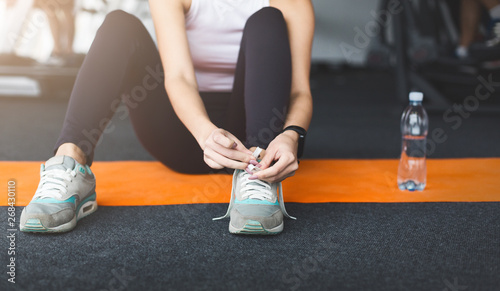 Valokuva  Ready for training. Woman tying laces preparing for workout