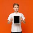 Leinwandbild Motiv Little boy showing digital tablet with blank screen