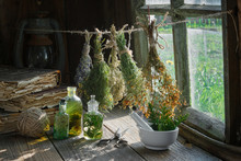 Tincture Or Infusion Bottles, Old Books, Mortar And Hanging Bunches Of Dry Medicinal Herbs. Herbal Medicine.