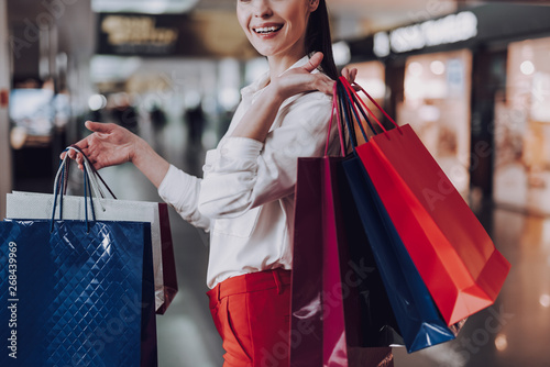 Cheerful woman is pleased with shopping at airport