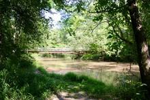 Iron Bridge Over Bend In Muddy Louisiana River Swamp