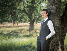 Portrait Young Man In Business Suit Leaning Against A Tree