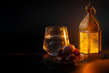 Muslim Religious Tradition, Holy Month Of Ramadan, Islam And Iftar Concept Theme With A Bowl Of Dates, Prayer Beads, Glass Of Water And Arabic Lantern On Black Background With Copy Space