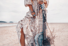 Close Up Of Fashionable Young Woman Legs. Fashion Model With Guitar Outdoors At Sunset