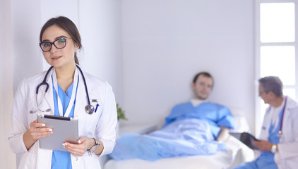 Doctor checking heart beat of patient in bed with stethoscope