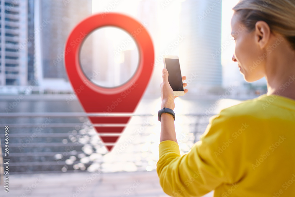 Fototapeta Young woman using smartphone on the city embankment with 3d red location pin GPS pointer on the background.