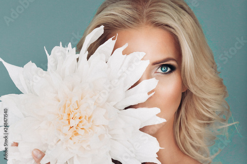 beautiful young blond blue-eyed woman with make-up and hairdress in white clothes holds a large white flower covering half of his face, looking directly at the blue background isolated