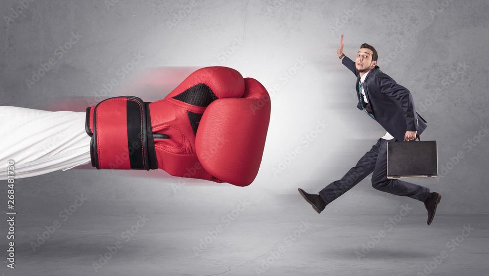 Leinwandbild Motiv - ra2 studio : Businessman gets a hit from a giant hand with boxing gloves