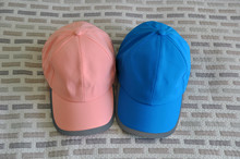 Pink And Blue Baseball Cap On A Printed Fabric Background. Space For Text.
