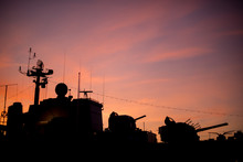 Silhouette Of A Retired Warship Against A Firey Red Sunset.