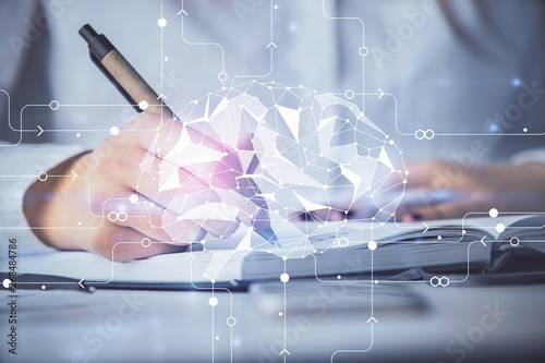 Fotografía  Double exposure of woman's writing hand on background with brain hologram