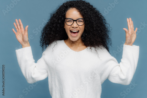 Fotografie, Obraz  Overjoyed mixed race woman with curly hair, raises hands, exclaims from positive emotions, keeps mouth opened, dressed in white sweater, stands against blue background