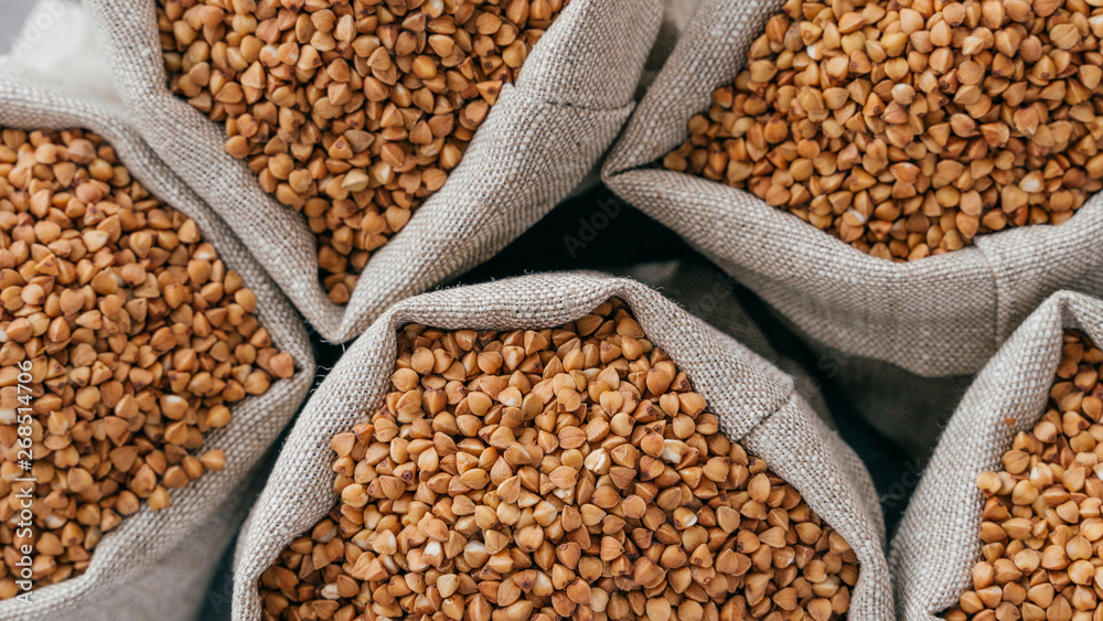 Fototapety, obrazy: Food and healthy eating concept. Close up shot of raw buckwheat in sacks. Nurture. Dry healthy cereals. Food ingredients. Top view
